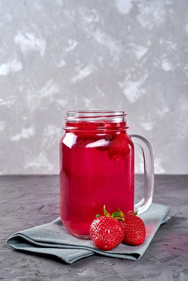 Selbst gemachtes süßes Erdbeerkompott im Glasweckglas auf grauem konkretem Steinhintergrund, Kopienraum Kaltes Sommerbeerengeträn stockfotos