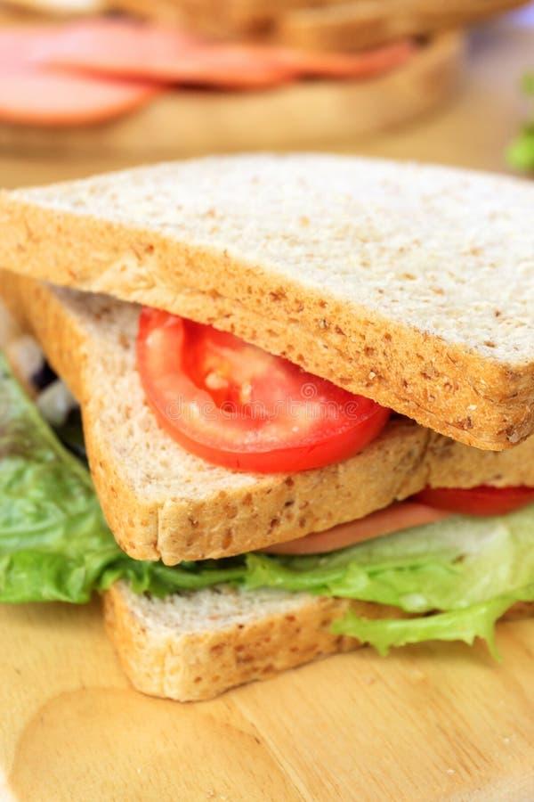 Selbst gemachtes Sandwichfr?hst?cksvorbereiten Abschluss herauf Vollweizensandwichbrot mit den Scheibentomaten und -kopfsalat ges stockfoto