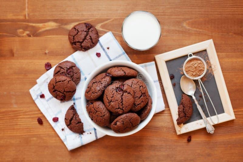 Selbst gemachtes Schokoladensplitterplätzchen oder -keks mit getrockneten Moosbeeren und Milch auf Holztisch stockfoto