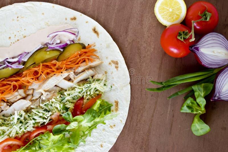 Selbst gemachtes Shawarma mit Hühnerfleischleiste und Frischgemüse über hölzernem Brett Abschluss oben lizenzfreie stockfotos