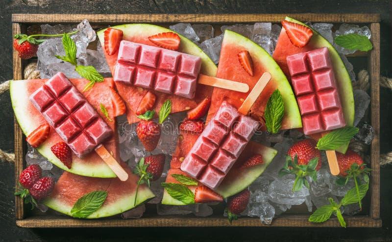 Selbst gemachtes Wassermelonenerdbeereis am stiel im hölzernen Behälter lizenzfreie stockfotografie