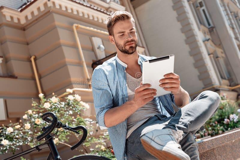 Selbst-Glaube und harte Arbeit erwerben Ihnen Erfolg immer Junger lächelnder Mann, der im Park, seine Tablette halten sitzt seins lizenzfreies stockfoto