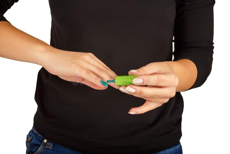 Selbst-Maniküre, Mädchen malt ihre Nägel im Grün stockfotografie
