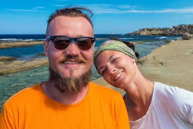 Selbstporträt von lächelnden Paartouristen auf den Ferien, die an streight Kamera mit blauem Mittelmeer untersuchen lizenzfreies stockbild
