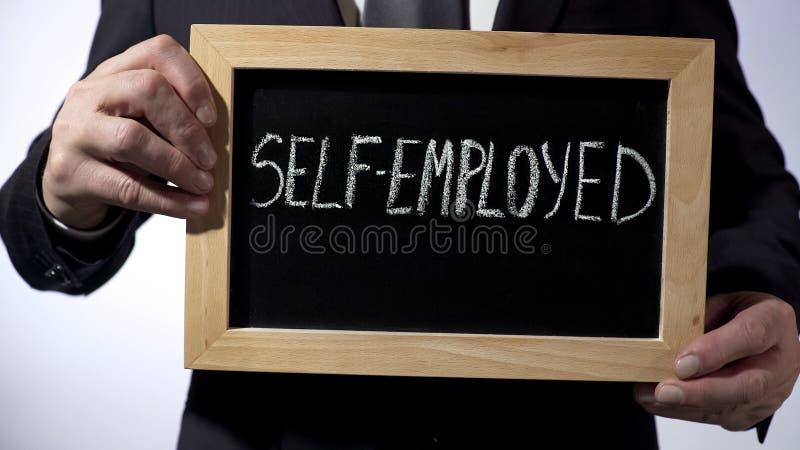 Selbstständiges geschrieben auf Tafel, Geschäftsmann, der Zeichen, Geschäftskonzept hält stockfotografie