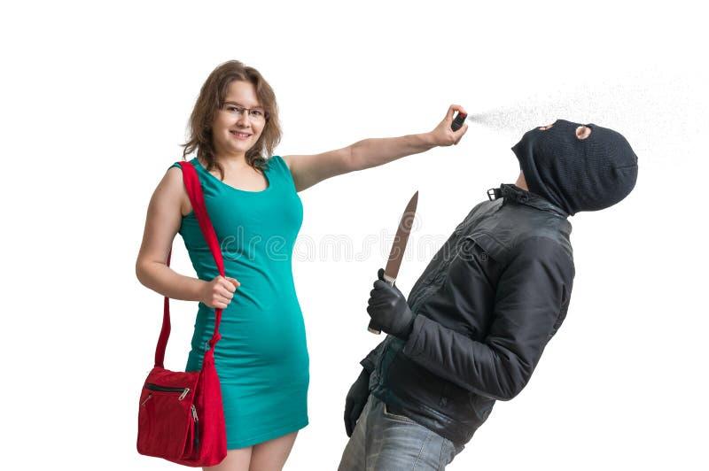 Selbstverteidigungskonzept Junge Frau verteidigt sich mit Pfefferspray stockfotografie