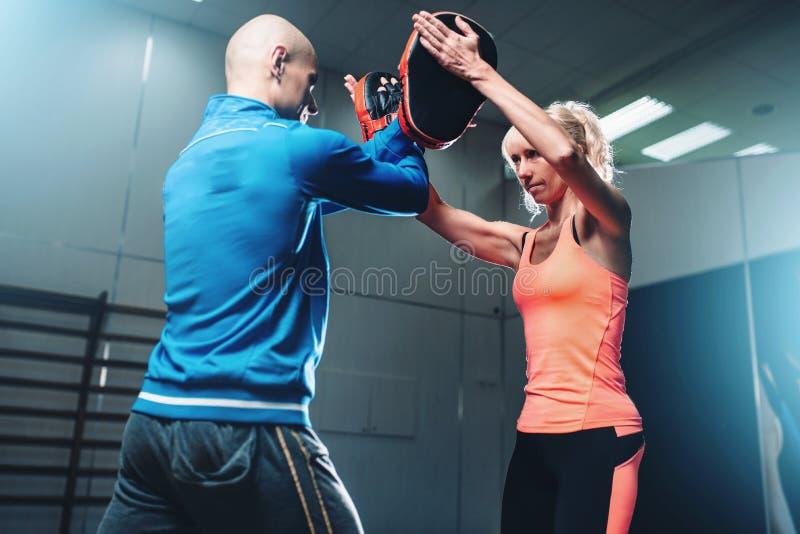 Selbstverteidigungstraining der Frauen mit persönlichem Trainer stockbild