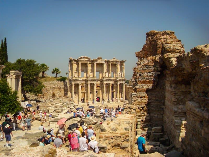 Selcuk, Turkey - June 18 2012 : Tourist visiting Ephesus Ancient City, near Kusadasi. UNESCO World Heritage Site. Celcius Library. In the background royalty free stock photo