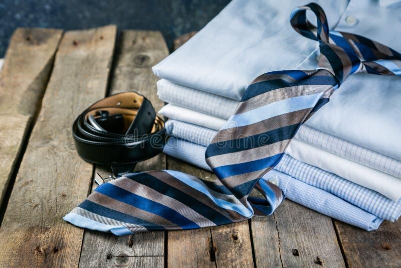 Seleção da roupa masculina - pilha de camisas dobradas, laço, correia, botão de punho imagem de stock royalty free