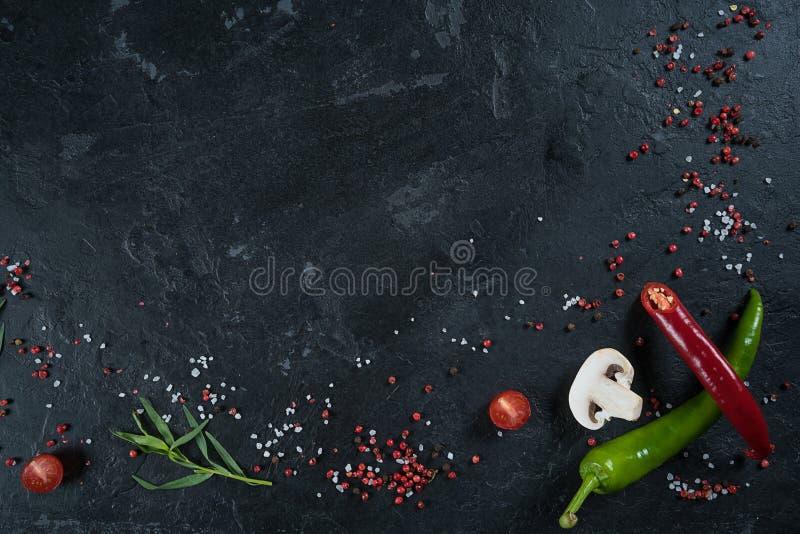 Seleção de ervas e de verdes das especiarias Ingredientes para cozinhar Fundo do alimento na tabela preta da ardósia fotografia de stock