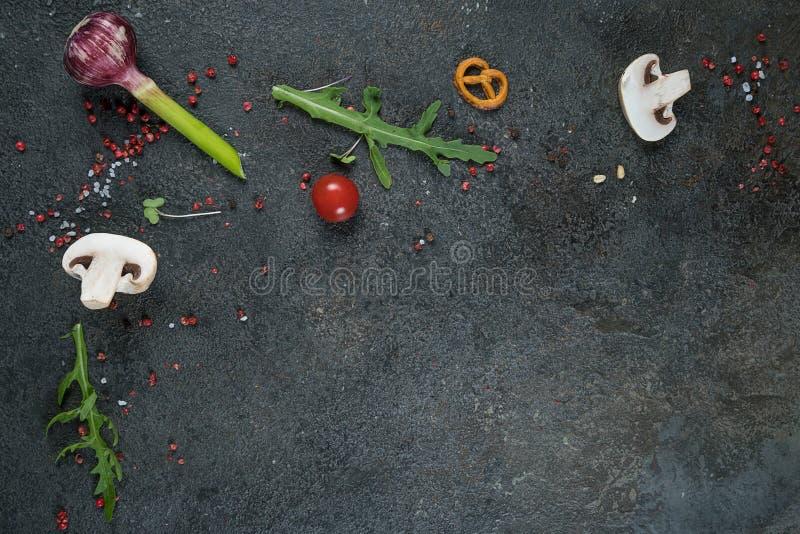 Seleção de ervas e de verdes das especiarias Ingredientes para cozinhar Fundo do alimento na tabela preta da ardósia imagens de stock