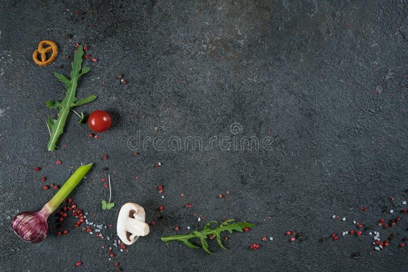 Seleção de ervas e de verdes das especiarias Ingredientes para cozinhar Fundo do alimento na tabela preta da ardósia foto de stock