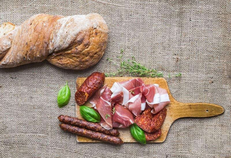 Seleção dos aperitivos da carne e um naco do pão rústico da vila sobre foto de stock royalty free
