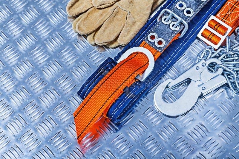 Sele och handskar för konstruktionshjälpmedelsäkerhet på det korrugerade arket av metall arkivbilder