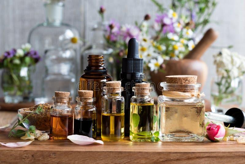 Selección de aceites esenciales con las hierbas y las flores imágenes de archivo libres de regalías
