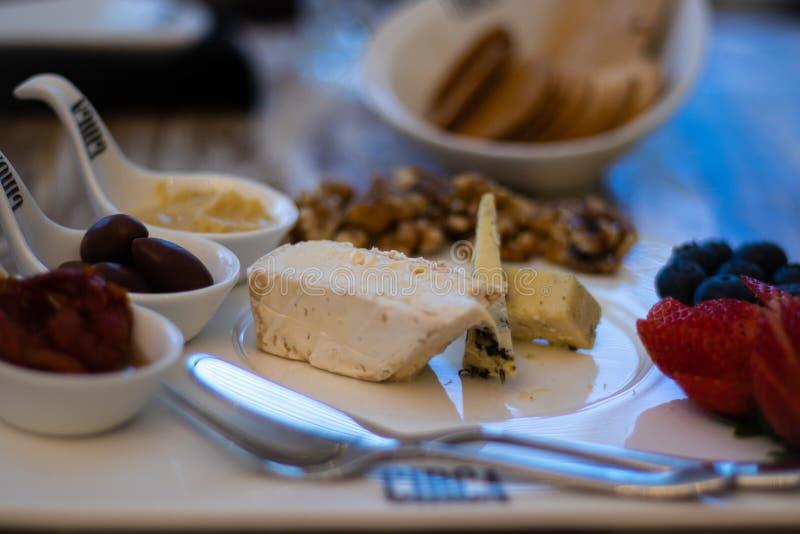 Selección de bizcochos y quesos en bandeja blanca con frutas y refrescos fotos de archivo libres de regalías