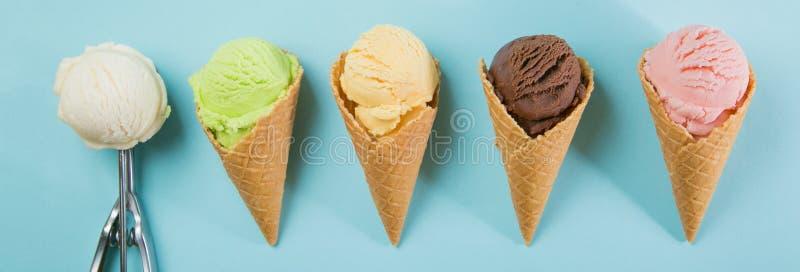 Selección de cucharadas coloridas del helado en fondo azul imágenes de archivo libres de regalías