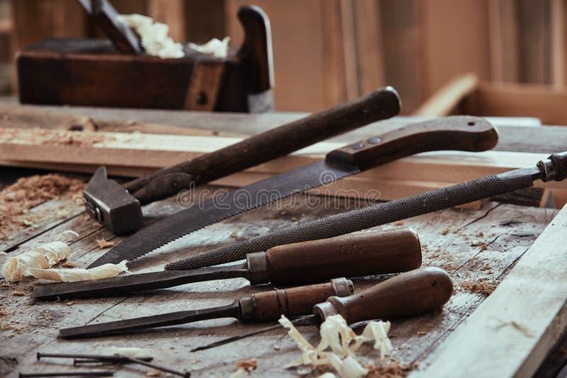 Selección de herramientas viejas en un banco de trabajo de la carpintería foto de archivo