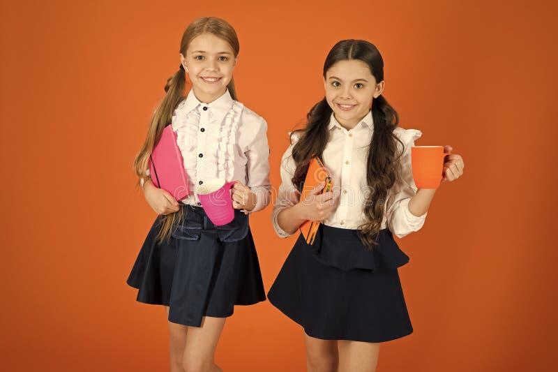 Selecci?n del t? para las colegialas lindas del desayuno que sostienen las tazas y los libros Peque?as muchachas que gozan del de imagenes de archivo