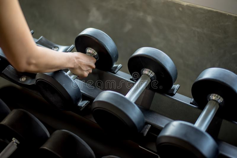 Select the appropriate dumbbell in Gym. Dumbbells on rack in fitness center royalty free stock image