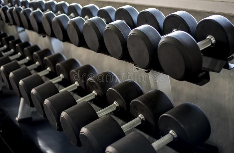 Select the appropriate dumbbell in Gym. Dumbbells on rack in fitness center stock image