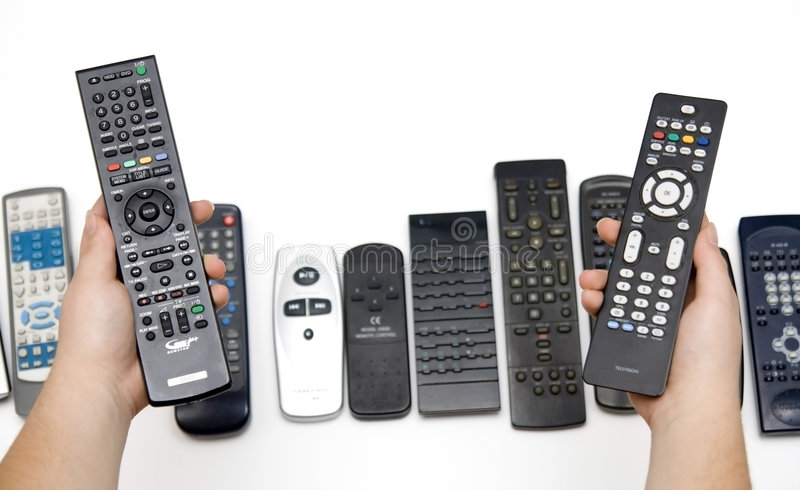 Many Assorted Remote Controls in Hands royalty free stock photo