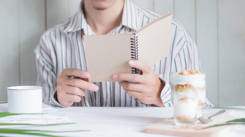 Select focus Asian male holding notebook with blur Healthy meal made of granola in glass foreground stock photo