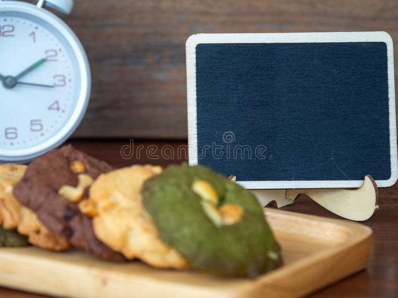 Select focus of blackboard behind of multiple color cookies inclusive peanut butter, green tea cookies, and Chocolate Chip Cookies royalty free stock images