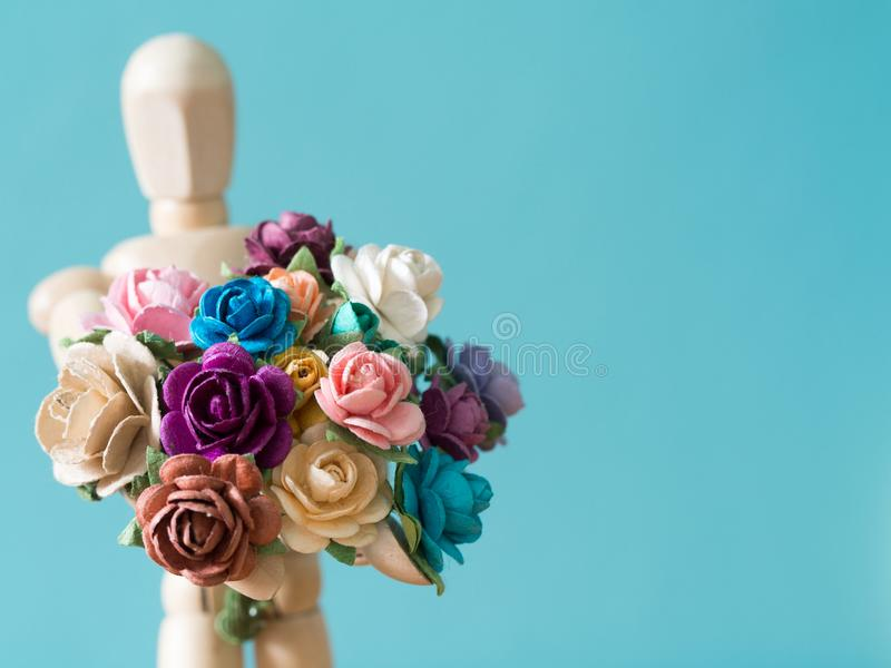 Select focus of flower. The wooden puppet holds flower and standing on the wood table. the background is blue and copy space. For text stock photography