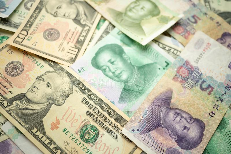 Select focus of 10 US dollar stack under China yuan banknote. Concept of Trade war between the United States and China royalty free stock photography