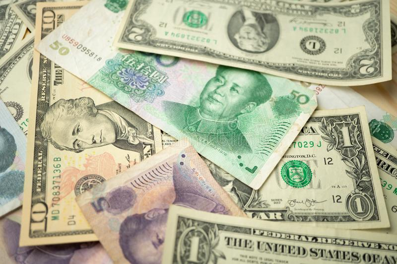 Select focus of 10 US dollar stack under China yuan banknote. Concept of Trade war between the United States and China stock photo