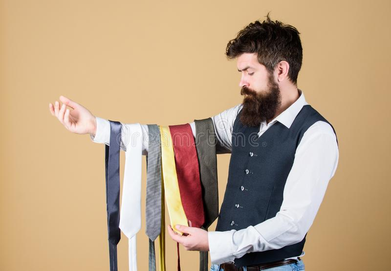 Select tie that has colors of your suit and shirt as well as at least one other color to provide an accent. Man bearded. Hipster hold few neckties. Guy with royalty free stock photos
