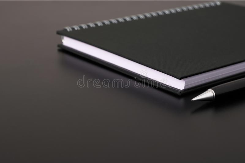 Selected focus black spiral notebook or diary and black pen on black desk stock photos
