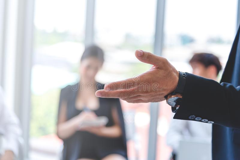 Selected focus on businessman hand opened asking for opinion in the meeting room with blurred background of team member stock images
