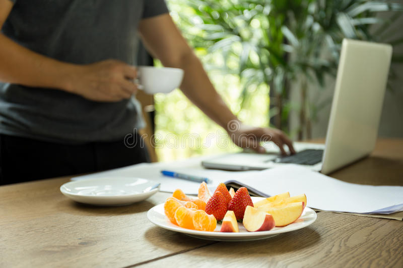 Selected focus fresh fruit with man holding cup of coffee working on laptop royalty free stock images