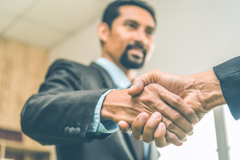 Selected focus on two businessman hands shake in the meeting room. Businessmand hand shake as a greeting royalty free stock image