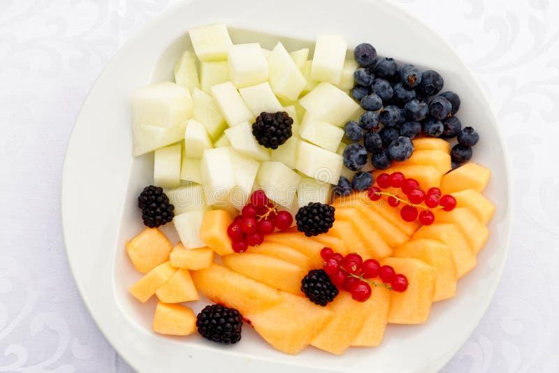 Selectie van besnoeiing op fruit en bessen op een witte ceramische plaat F royalty-vrije stock afbeelding