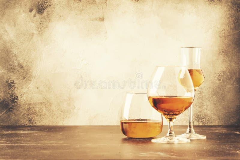 Selectie van harde sterke alcoholische dranken en geesten in assortiment: cognac, brandewijn en rum Grijze bar tegenachtergrond, royalty-vrije stock afbeeldingen