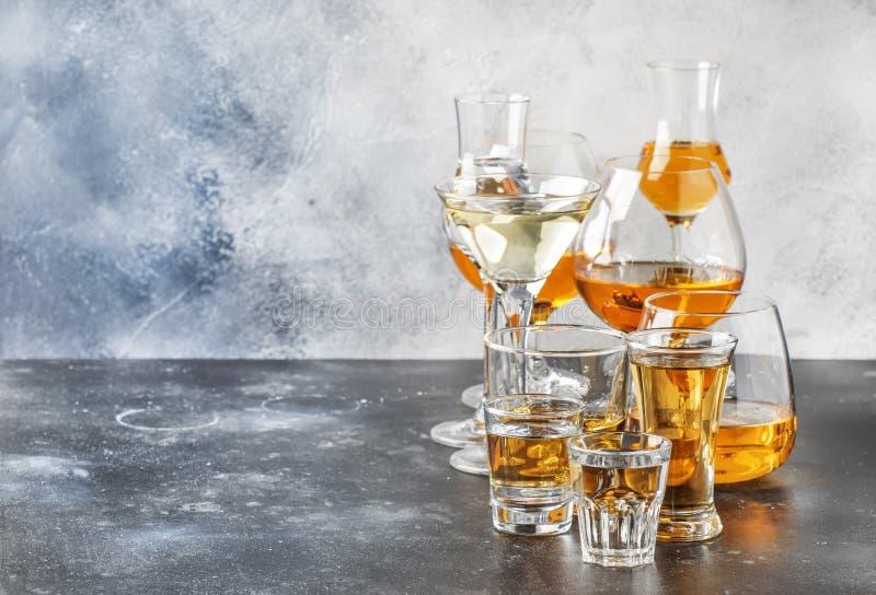 Selectie van harde sterke alcoholische dranken in grote glazen en klein geschoten glas in assortent: wodka, rum, cognac, tequila, stock afbeelding