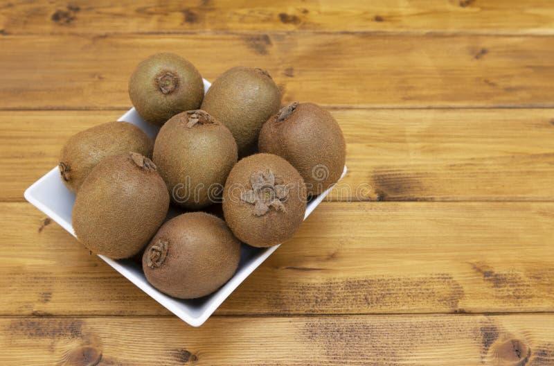Selectie van harig-gevild kiwifruit in een kom op een lijst royalty-vrije stock foto
