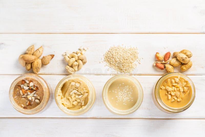 Selectie van nootboters - pinda, cachou, amandel en sesamzaden stock foto