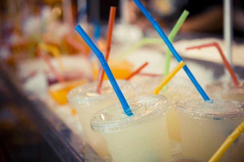 Selectie van plastic koppen met grapefruit juice en gekleurd stro stock foto's