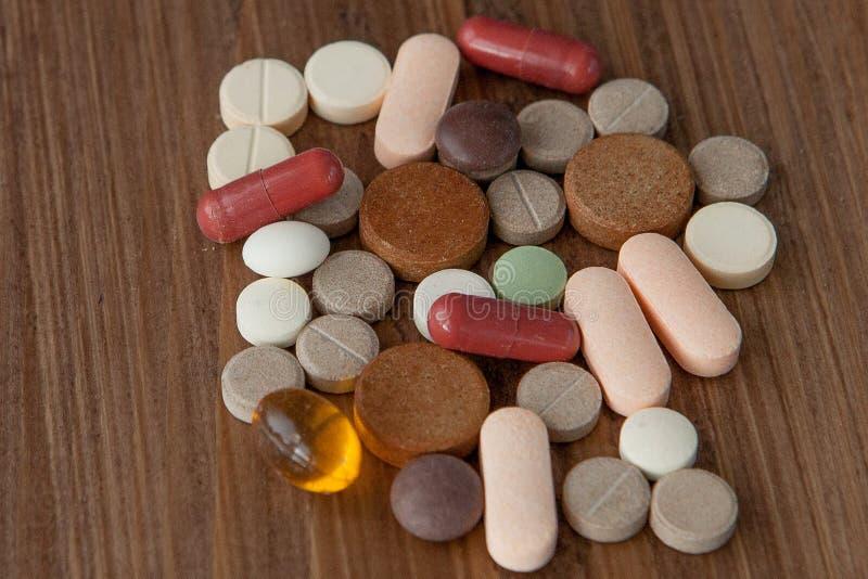 Selectieve die nadruk op pil op houten achtergrond wordt uitgespreid globaal gezondheidszorgconcept Farmaceutische Industrie Drug royalty-vrije stock afbeelding