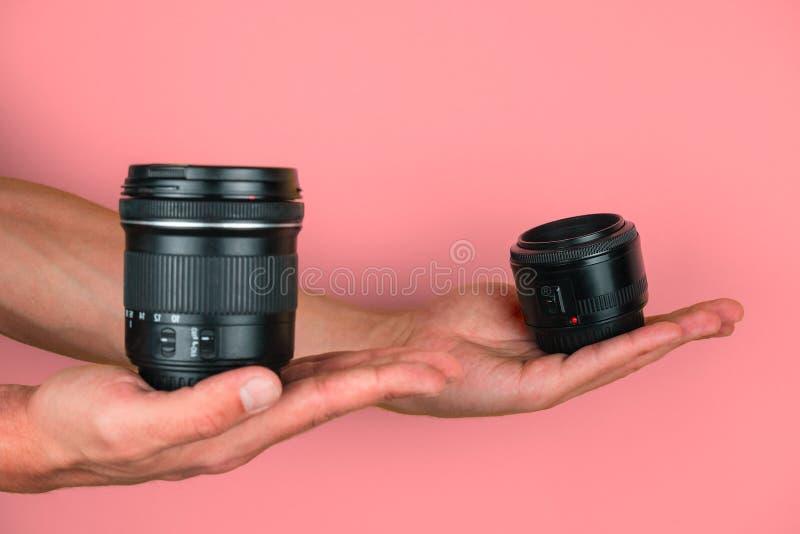 selectieve focushanden houden camera-lenzen vast op een roze achtergrond, vergelijking en keuze uit professioneel optisch concept stock afbeelding