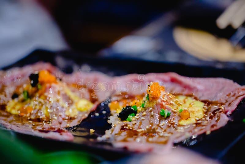 Selectieve focust aan reeks van geroosterde Wagyu-rundvleessushi met vissenkuiten en Tobiko op zwarte plaat in Japans restaurant royalty-vrije stock foto