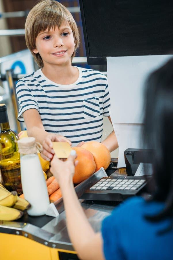 selectieve nadruk die van jongen betaling met creditcard verrichten op contant geldpunt stock afbeelding