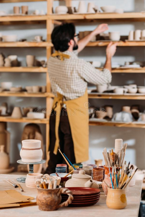 selectieve nadruk die van pottenbakker zich bij planken met ceramische dishwareborstels en verven op lijst bevinden stock foto's