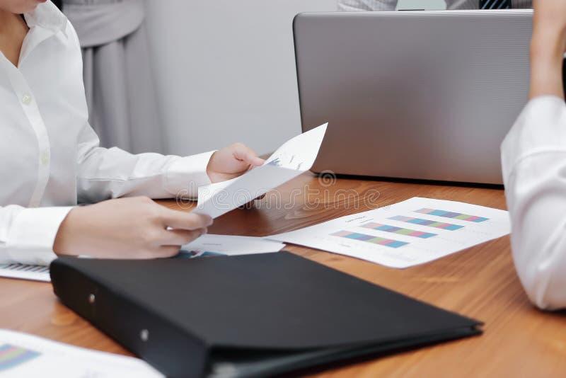 Selectieve nadruk en ondiepe diepte van gebied Administratie of grafieken met bedrijfsmensen tussen vergadering in bureau stock fotografie