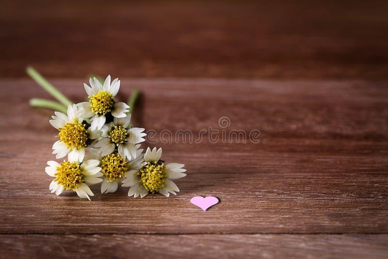 Selectieve nadruk gele bloemen met roze hart op grunge uitstekende houten lijst stock afbeeldingen