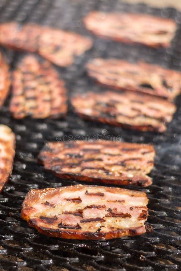 Selectieve nadruk op het bacon op de hete grill met ondiepe diepte van mening stock fotografie